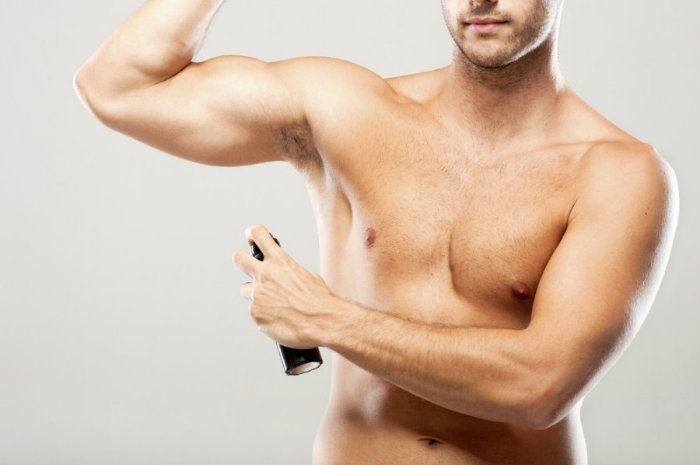 Fit men putting deodorants